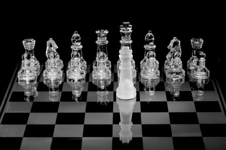 Chess board complete with pieces made of glass. photo