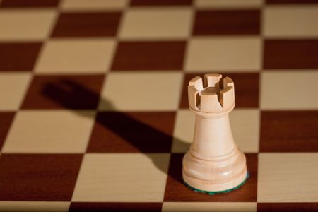 Chess piece - a white rook on a chessboard. photo