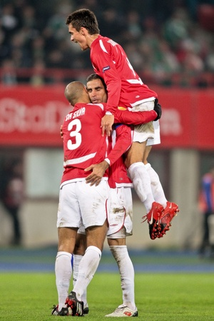 VIENNA,  AUSTRIA - NOVEMBER 5 SK Rapid loses 0:3 to Hapoel Tel Aviv on November 5, 2009 in Vienna, Austria. Shown are defender  Douglas da Silva (Hapoel, #3) and his team celebrating the second goal. Stock Photo - 8465396