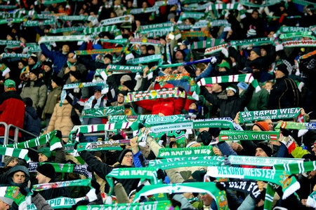glasgow: VIENNA,  AUSTRIA - DECEMBER 17 SK Rapid plays 3:3 to Celtic Glasgow on December 17, 2009 in Vienna, Austria. Shown are fans of SK Rapid celebrating their team.
