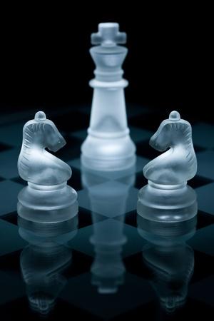tablero de ajedrez: Tiro de macro de piezas de ajedrez de vidrio contra un fondo negro