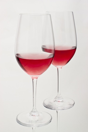 Two glasses of red wine in soft white light