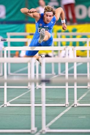 VIENNA, AUSTRIA - FEBRUARY 19: Indoor track and field championship. Manuel Prazak (#212, Austria) wins the mens 60m hurdles event on February 19, 2011 in Vienna, Austria.