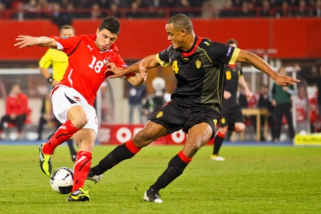 VIENNA,  AUSTRIA - MARCH 25 Austria loses to Belgium 0:2 in a qualifying match for EURO 2012 on March 25, 2011  in Vienna, Austria. Shown are Uemit Korkmaz (#18, Austria) and Vincent Kompany (#4, Belgium). Stock Photo - 9158264