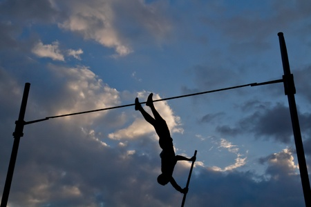 Silhouette of a pole vaulter against a dramatic cloudscape.