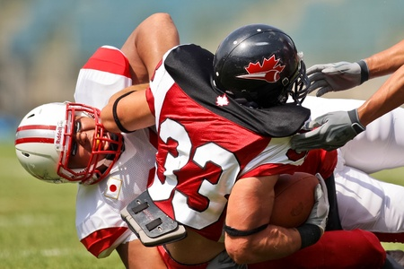 gridiron: GRAZ, AUSTRIA - JULY 13 RB Matt Walter (#33 Canada) is tackled at the Football World Championship on July 13, 2011 in Graz, Austria. Canada wins 31:27 against Japan.