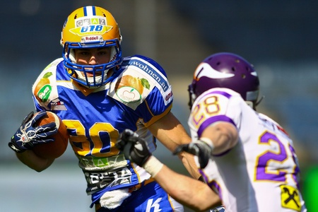 putz: GRAZ, AUSTRIA - APRIL 9 WR Wolfrum Hofbauer (#80 Giants) is tackled bz DB Christoph Putz (#28 Vikings) on April 9, 2011 in Vienna, Austria. The Graz Giants beat the Vienna Vikings 21:14.