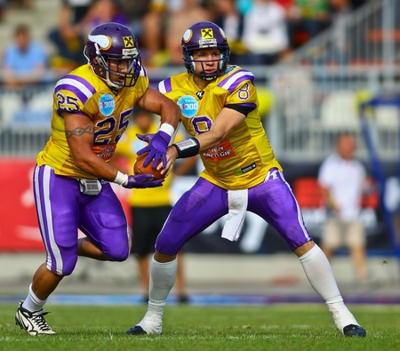 VIENNA, AUSTRIA - JUNE 12 QB Christoph Gross (#8 Vikings) hands off the ball to RB Josiah Cravalho (#25 Vikings) on June 12, 2011 in Vienna, Austria. The Vienna Vikings beat the Graz Giants 19:14.