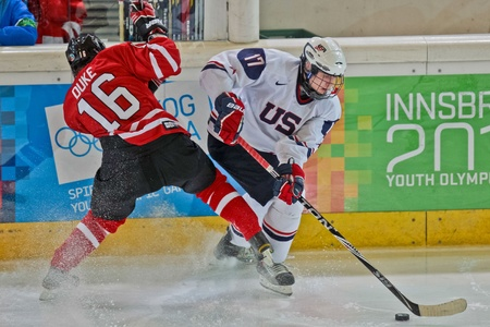 INNSBRUCK, AUSTRIA - JANUARY 15 Reid Duke (Canada) and Joe Wegwerth (USA) fight for the puck as Canada beats the USA 5:1 in the mens ice hockey tournament on January 15, 2012 in Innsbruck, Austria.