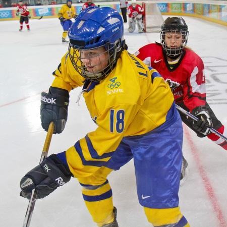 INNSBRUCK, AUSTRIA - JANUARY 17 Amanda Lindberg (Sweden) and Paulina Polczik (Austria) fight for the puck as Sweden beats Austria 3:0 in the ladies ice hockey tournament on January 17, 2012 in Innsbruck, Austria.