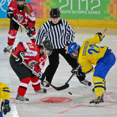 INNSBRUCK, AUSTRIA - JANUARY 17 Tamara Grascher (Austria) and Johanna Eidenstein fight for the puck as Sweden beats Austria 3:0 in the ladies' ice hockey tournament on January 17, 2012 in Innsbruck, Austria. Stock Photo - 12160249