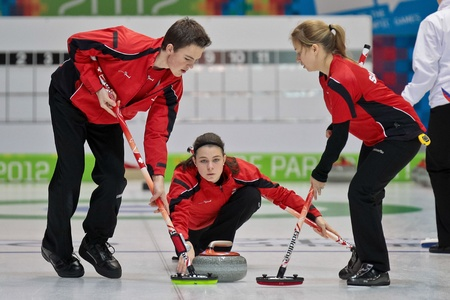 INNSBRUCK, AUSTRIA - JANUARY 17 Michael Brunner, Elena Stern and Lisa Gisler of team Switzerland beat the Czech Republic 8:4 in the curling tournament on January 17, 2012 in Innsbruck, Austria.