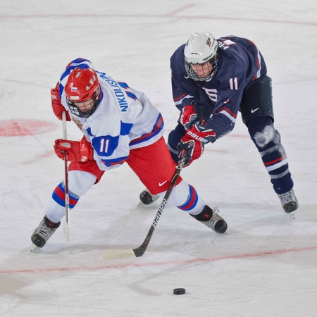 INNSBRUCK, AUSTRIA - JANUARY 18 Ivan Nikolishin (Russia) and Jared Fiegl(USA) fight for the puck as Russia beats the USA 7:1 in the mens ice hockey tournament on January 18, 2012 in Innsbruck, Austria.