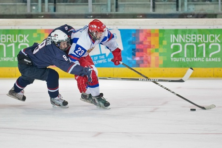 innbruck: INNSBRUCK, AUSTRIA - JANUARY 18 Kevin Kerr (USA) and Maxim Lazarev (Russia) fight for the puck as Russia beats the USA 7:1 in the mens ice hockey tournament on January 18, 2012 in Innsbruck, Austria.