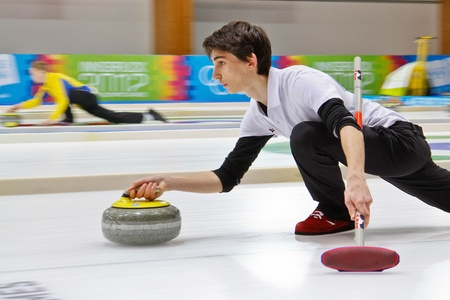 INNSBRUCK, AUSTRIA - JANUARY 20 Alessandro Zoppi (Italy) and his partner from Estonia lose 10:3 to Russia and the Czech Republic in the curling mixed doubles on January 20, 2012 in Innsbruck, Austria.