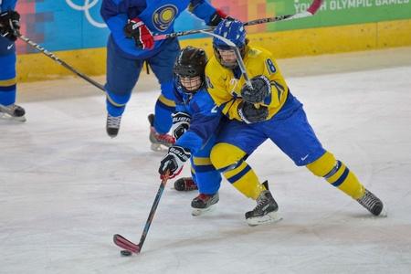 yog: INNSBRUCK, AUSTRIA - JANUARY 20 Amanda Lindberg (Sweden) and Zhanna Nurgaliyeva (Kazachstan) fight for the puck as Sweden beats Kazachstan 11:0 in the ladies ice hockey tournament on January 20, 2012 in Innsbruck, Austria.