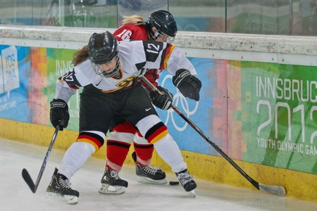 INNSBRUCK, AUSTRIA - JANUARY 20 Anna Fiegert (Germany) and Anna Meixner (Austria) fight for the puck as Austria beats Germany 2:0 in the semifinals of the ice hockey tournament on January 20, 2012 in Innsbruck, Austria. Stock Photo - 12160221