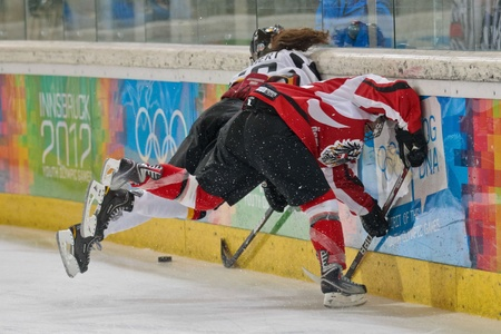 INNSBRUCK, AUSTRIA - JANUARY 20 Anna Fiegert (Germany) and Paulina Polczik (Austria) fight for the puck as Austria beats Germany 2:0 in the semifinals of the ice hockey tournament on January 20, 2012 in Innsbruck, Austria.