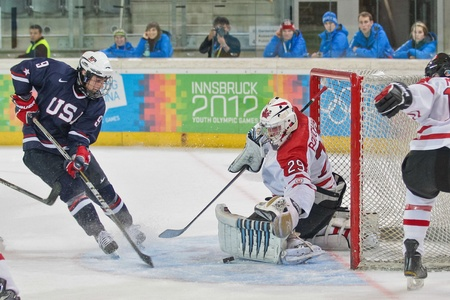 innbruck: INNSBRUCK, AUSTRIA - JANUARY 21 Shane Gersich (USA) tries to score a goal a his team loses 7:5 toin the mens ice hockey tournament on January 21, 2012 in Innsbruck, Austria.
