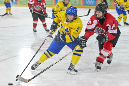 INNSBRUCK, AUSTRIA - JANUARY 22 Mathildah Andersson (Sweden) and Martina Kness (Austria) fight for the puck as Sweden beats Austria 3:0 in the ladies ice hockey tournament and wins the gold medal on January 22, 2012 in Innsbruck, Austria.