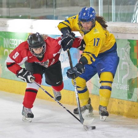 INNSBRUCK, AUSTRIA - JANUARY 22 Anna Johansson (Sweden) and Paulina Polczik (Austria) fight for the puck as Sweden beats Austria 3:0 in the ladies' ice hockey tournament and wins the gold medal on January 22, 2012 in Innsbruck, Austria. Stock Photo - 12160194