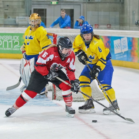 INNSBRUCK, AUSTRIA - JANUARY 22 Lina Backlin (Sweden) and Anna Meixner (Austria) fight for the puck as Sweden beats Austria 3:0 in the ladies ice hockey tournament and wins the gold medal on January 22, 2012 in Innsbruck, Austria.