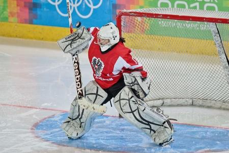 innbruck: INNSBRUCK, AUSTRIA - JANUARY 22 Paula Marchhart (Austria) stops the puck as Sweden beats Austria 3:0 in the ladeis ice hockey tournament and wins the gold medal on January 22, 2012 in Innsbruck, Austria. Editorial