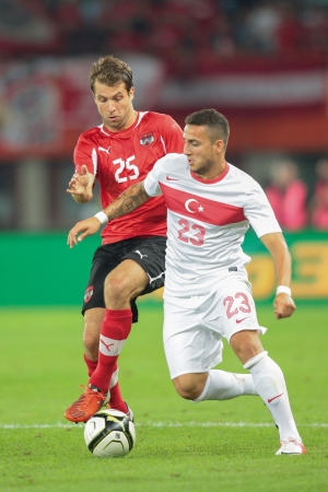 VIENNA,  AUSTRIA - AUGUST 15 Andreas Ivanschitz (#25 Austria) and Sercan Sararer (#23 Turkey) fight for the ball during the friendly soccer game on August 15, 2012 in Vienna, Austria.