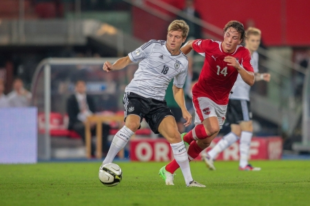 VIENNA,  AUSTRIA - SEPTEMBER 11 Toni Kroos (#18 Germany) and Julian Baumgartlinger (14 Austria) fight for the ball during the WC qualifier soccer game on September 11, 2012 in Vienna, Austria.