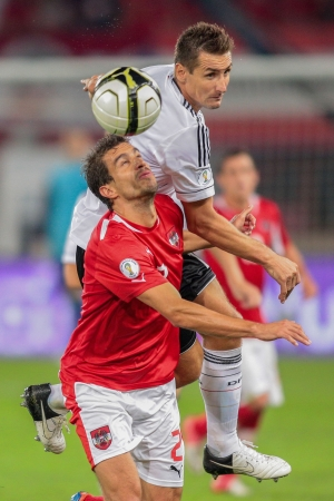 VIENNA, AUSTRIA - SEPTEMBER 11 Miroslav Klose (#11 Germany) and Gyoergy Garics (#2 Austria) fight for the ball during the WC qualifier soccer game on September 11, 2012 in Vienna, Austria.