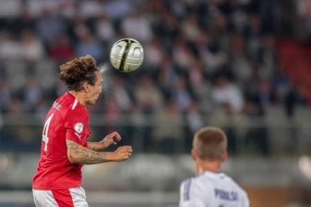 VIENNA,  AUSTRIA - SEPTEMBER 11 Emanuel Pogatetz (#4 Austria) heads the ball during the WC qualifier soccer game on September 11, 2012 in Vienna, Austria.
