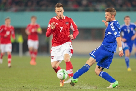 qualifier: VIENNA,  AUSTRIA - MARCH 22 Marko Arnautovic (#7 Austria) and Rogvi Baldvinson (#5 Faroe Islands) fight for the ball during the world cup qualifier game on March 22, 2013 in Vienna, Austria. Editorial