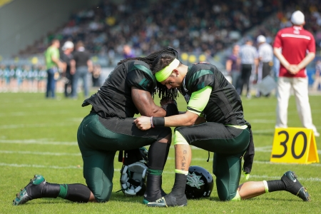 afl: VIENNA,  AUSTRIA - APRIL 21 QB Jonathan Dally (#8 Dragons) and RB Tunde Ogun (#1 Dragons) pray before the AFL football game on April 21, 2013 in Vienna, Austria. Editorial