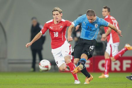 15 18: KLAGENFURT, AUSTRIA - MARCH 05, 2014: Christoph Leitgeb (#18 Austria) and Diego Perez (#15 Uruguay) fight for the ball in a friendly soccer game between Austria and Uruguay.
