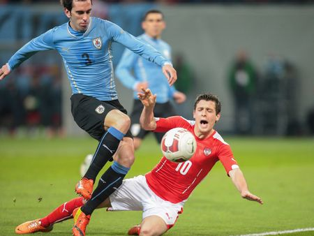team cooperation: KLAGENFURT, AUSTRIA - MARCH 05, 2014: Diego Godín (#3 Uruguay) and Zlatko Junuzovic (#10 Austria) fight for the ball in a friendly soccer game between Austria and Uruguay.