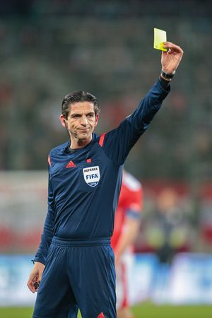 KLAGENFURT, AUSTRIA - MARCH 05, 2014: Referee Deniz Aytekin (Germany) show a yellow card in a friendly soccer game between Austria and Uruguay.