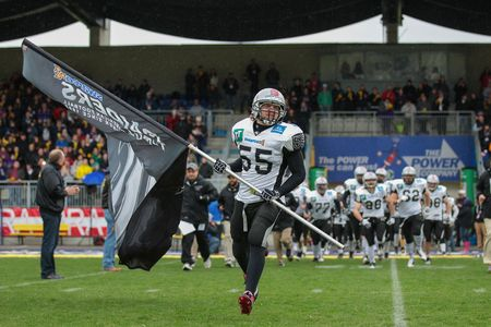 afl: VIENNA, AUSTRIA - MARCH 23, 2014: LB Christoph Schilcher (#55 Raiders) leads his team on the field before an AFL football game.