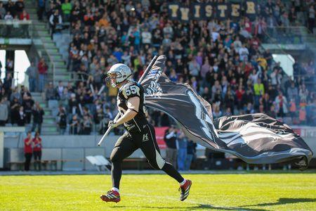innbruck: INNSBRUCK, AUSTRIA - MARCH 29, 2014: LB Christoph Schilcher (#55 Raiders) leads his team on the field before an AFL football game.