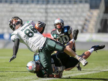 INNSBRUCK, AUSTRIA - MARCH 29, 2014: WR Georg Pongratz (#86 Dragons) is tackled by LB Stefan Werner (#46 Raiders) in an AFL football game.