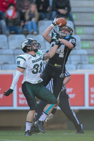 INNSBRUCK, AUSTRIA - MARCH 29, 2014: CB Christian Kober (#31 Dragons) and WR Clemens Erlsbacher (#84 Raiders) fight for the ball in an AFL football game. Editorial