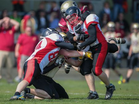 legionaries: WINDEN, AUSTRIA - APRIL 12, 2014: RB Thomas Weis (#23 Spartans) is tackled by DB Christopher Moritz (#24 Legionaries). Editorial