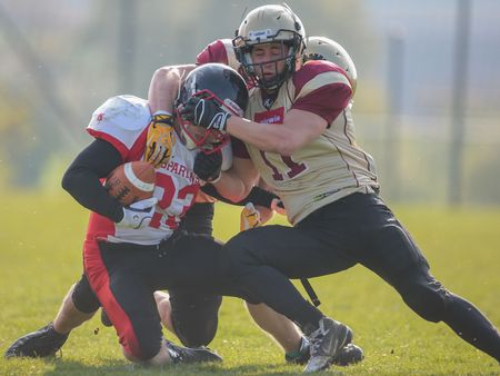 WINDEN, AUSTRIA - APRIL 12, 2014: RB Thomas Weis (#23 Spartans) is tackled by DB Peter Gaudek (#11 Legionaries). Editorial