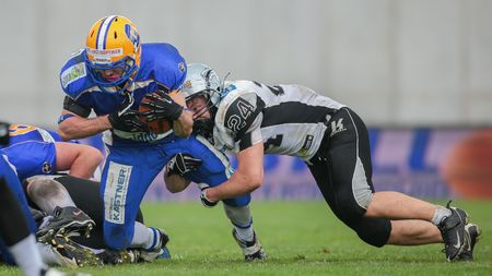 24 26: GRAZ, AUSTRIA - APRIL 26, 2014: RB Alexander Sanz (#1 Giants) is tackled by LB Fabian Seeber (#24 Raiders). Editorial