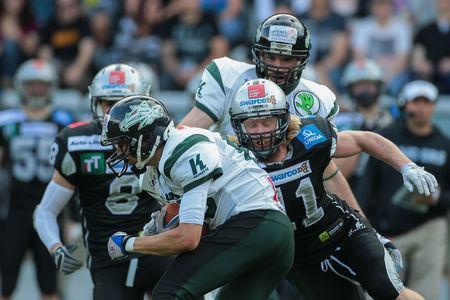 db: INNSBRUCK, AUSTRIA - JULY 12, 2014: DB Enrico Martini (#11 Raiders) tackles the ball carrier during an Austrian football league game. Editorial