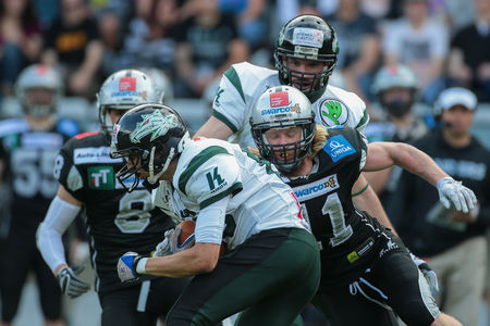 INNSBRUCK, AUSTRIA - JULY 12, 2014: DB Enrico Martini (#11 Raiders) tackles the ball carrier during an Austrian football league game. Editorial