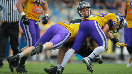 football tackle: VIENNA, AUSTRIA - JULY 13, 2014: DB Andreas Lunzer (#29 Vikings) and DB Stefan Ruthofer (#9 Vikings) tackle WR Jakub Wolesky (#2 Panthers) during an Austrian football league game.