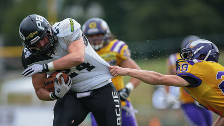 db: VIENNA, AUSTRIA - JULY 13, 2014: DB Andreas Lunzer (#29 Vikings) holds RB Adam Synacek (#24 Panthers) during an Austrian football league game.