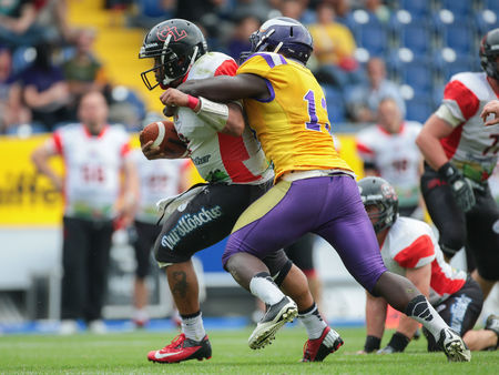 ST. POELTEN, AUSTRIA - JULY 26, 2014: LB Precious Ogbevoen (#13 Vikings) tackles QB Phillip Garcia (#2 Lions) during Silver Bowl XVII. Editorial