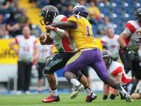 ST. POELTEN, AUTRICHE - 26 juillet 2014: LB Precious Ogbevoen (# 13 Vikings) aborde QB Phillip Garcia (# 2 Lions) pendant Argent Bowl XVII.