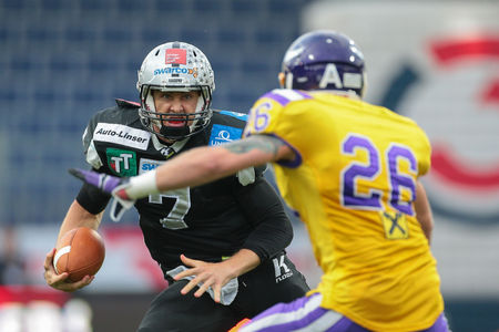 db: ST. POELTEN, AUSTRIA - JULY 26, 2014: DB Craig Sedunov (#26 Vikings) prepares to tackle QB John Van Den Raadt (#7 Raiders) during Austrian Bowl XXX.